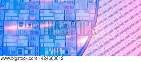 silicon wafer with microchips reflecting different colors.