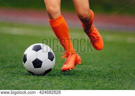 Soccer Player Hits The Ball On The Artificial Turf. Footballer In Sports Cleats Kicking Ball. Legs O