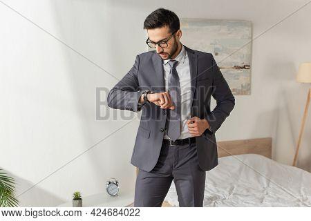 Businessman In Eyeglasses Looking At Wristwatch In Bedroom