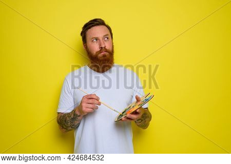 Undecided Man With Beard And Tattoo Is Ready To Draw With Brushes