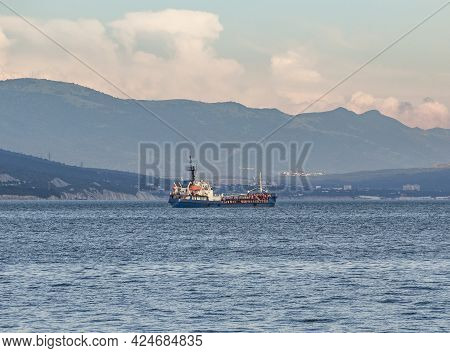 Fuel Tanker Or Bunker Ship Sailing On Water At Mountains Background