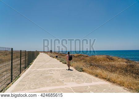Coastal Broadwalk Along Mediterranean Sea On Island Of Cyprus In City Of Paphos. Traveler With Backp