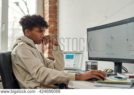 Side View Of Focused Young Guy Trader Looking At Computer Screen To Analyze Statistics While Sitting