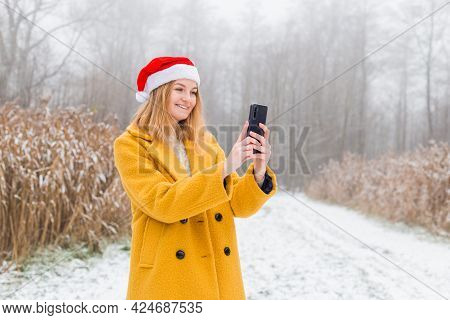 Young Blond Woman Wearing Yellow Coat Using Smart Phone App Over Nature Background, Trendy Color Of