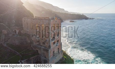 Tenerife, Spain - April 2 2021: Destroy And Ruin Factory In Front Of Shoreline Empty On A Hill. Aban