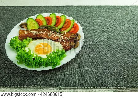 Fried Eggs With Bacon And Vegetables Are Served On A Plate. Fried Eggs With Bacon On The Table As A