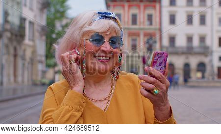 Senior Grandmother Woman Tourist With Smartphone, Smiling, Listening Music In App Wearing Earphones,