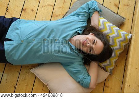 Woman Lies On Wooden Floor And Smiles. Moment Of Rest And Relaxation Of A Girl In A Good Mood.