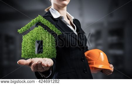 Real Estate Agent Holds In Palm Green Plant In Shape Of House. Woman In Business Suit With Safety He