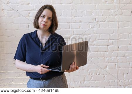 Portrait Of Young Brunette Woman With Shoulder Length Hair With Laptop In Her Hands And Looking At T