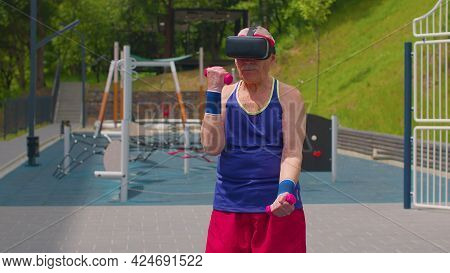 Active Mature Man Grandfather In Vr Headset Goggles Doing Sport Training Fitness Gymnastics Weightli