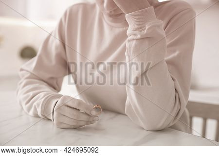 Woman Holding Wedding Ring At Table Indoors, Closeup. Cheating And Breakup