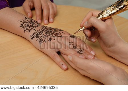 Master Making Henna Tattoo On Hand At Wooden Table, Closeup. Traditional Mehndi