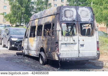 A Burnt-out Car On A City Street, Serious Fire Damage After A Fire On The Body Of A Passenger Minibu