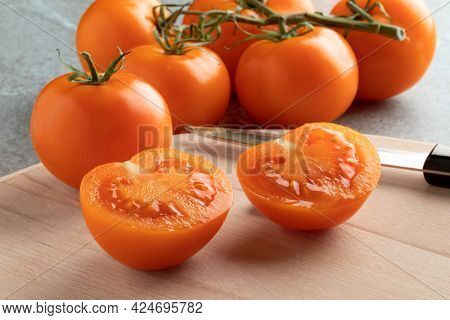 Whole and half fresh ripe juicy orange vine tomatoes on a cutting board close up