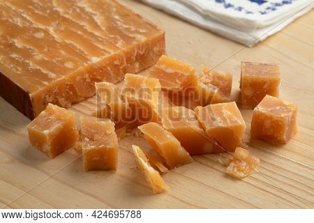 Cubes of old mature Dutch sheep milk cheese on a cutting board