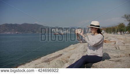Woman use cellphone to take photo at seaside