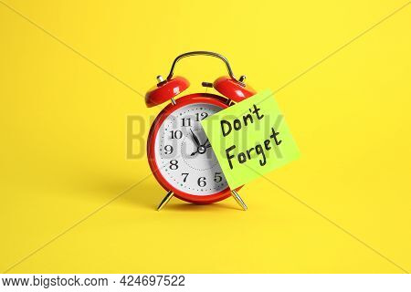 Alarm Clock And Reminder Note With Phrase Don't Forget On Yellow Background