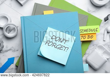 Reminder Note With Text Don't Forget And Stationery On White Marble Table, Flat Lay