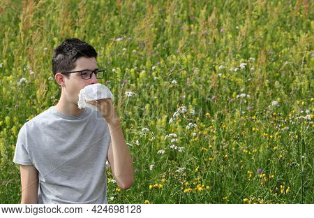 Young Myopic Boy With Asthma Sneezes On A Handkerchief Because Of Allergy To Grass On Flowery Field