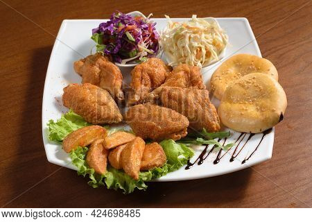 Pieces Of Chicken Fillet Fried In Batter On A Plate With Potatoes, Bread And Salad