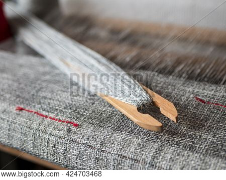 Wooden Shuttle With Mottled Yarn Is On The Hand Weaving Loom. Woven Grey Fabric With Red Stripes