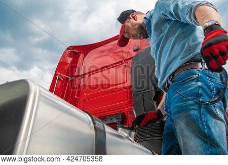 Caucasian Semi Truck Driver In His 30s Looking At Diesel Tank Cap Looking For Leaks Or Stolen Diesel