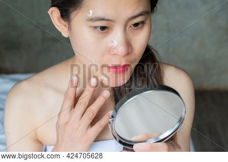 Portrait Of Asian Woman Looking In The Mirror And Applying Anti Aging Cream On Her Under Eyes. The A