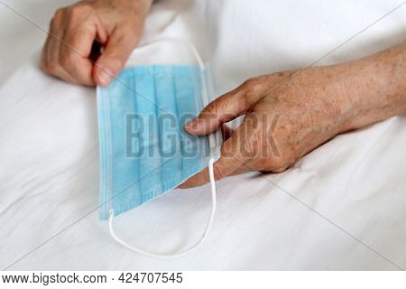 Wrinkled Hands Of Elderly Woman With Medical Face Mask. Coronavirus Protection For Old People