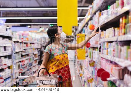 Asian Woman In Protective Mask Shopping In Supermarket During Covid-19 Pardemic