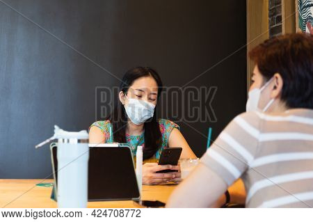 Two Woman Friends Ih Protective Mask Sitting On Cafe Looking Cell Phone