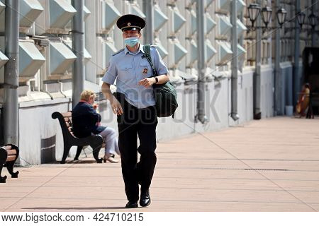 Moscow, Russia - June 2021: Russian Police Officer In Face Mask And Summer Uniform Walking By The St