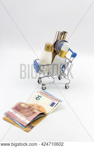 Cosmetics In The Shopping Cart And Euro Money On White Bacground