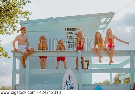 Six Cute Blond Kids In Summer Clothes Posing On The Sand Beach With Blue Lifeguard Tower And Surfboa