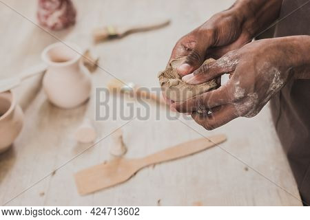 Partial View Of Young African American Man Sculpting Piece Of Clay With Hands Near Table With Equipm