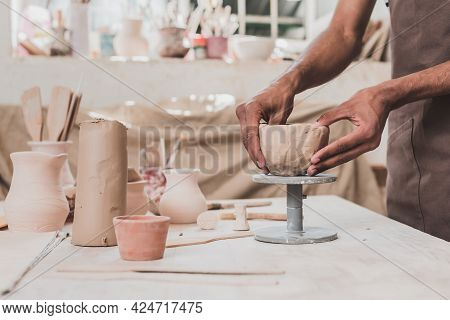 Partial View Of Young African American Man Sculpting Clay Pot With Hands On Table With Equipment In
