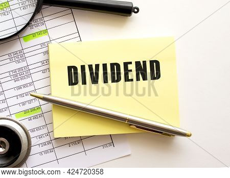 Dividend Text On A Sticker On Your Desktop. Pen And Magnifier. Financial Concept.