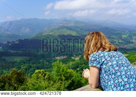 Woman Leaning Out Of A Viewpoint Contemplating The Green Landscape Of The Valley. Santander.