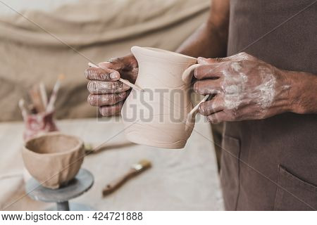Partial View Of Young African American Man Sculpting Clay Pot With Stick In Pottery