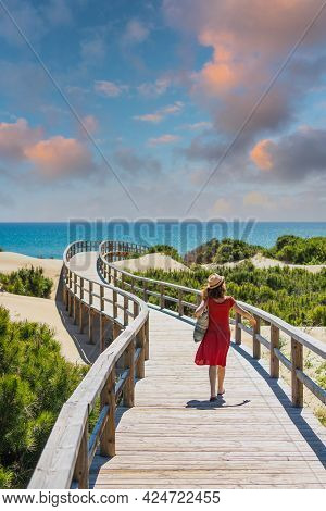 Girl With Red Dress On The Wooden Path To Playa Moncayo In Guardamar Del Segura Next To Torrevieja,