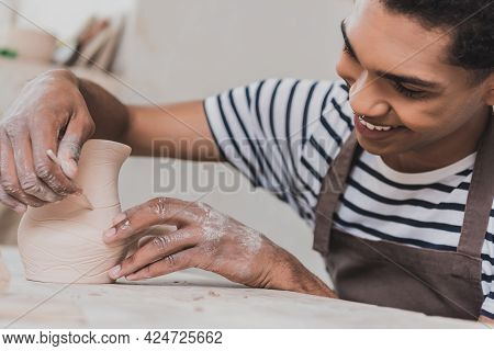 Positive Young African American Man Sculpting Clay Pot With Stick In Pottery