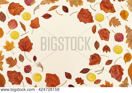 Autumn Round Frame From Dry Leaf And Fragrant Lit Candles On Neutral Beige Background With Copy Spac
