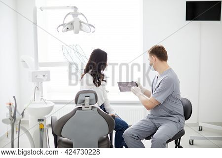 Male Dentist With Digital Tablet. Modern Treatment In Professional Dental Clinic.