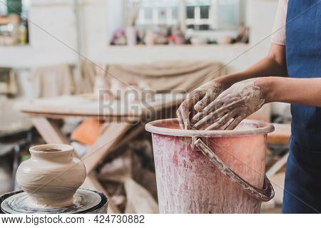 Partial View Of Young African American Woman In Apron Washing Hands In Bucket Near Sculpted Clay Pot