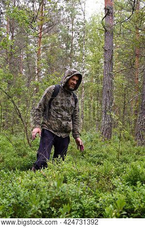 Man In Camouflage Clothing With A Backpack In The Woods. A Forester Walks Along A Path Through A Den