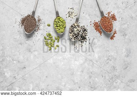 Various Seeds In Spoons On Gray Grunge Background. Pumpkin Seeds, Sesame Seeds, Flax Seeds, And Chia
