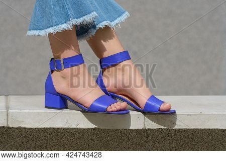 Womens Legs In Blue Denim Jeans And Sandals In The City Street. Trendy Elegant Casual Outfit. Detail