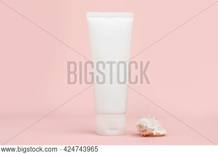 Front View Of Unbranded White Squeeze Bottle Cream Tube And Seashell On Pink Background. Cosmetics W
