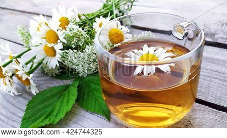 Chamomile Tea In A Glass Cup. Floral Background. A Bouquet Of Wildflowers In The Background. A Trans