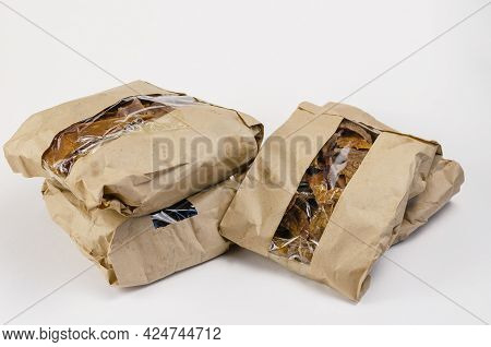 Pet Treats In Brown Paper Bags With Window. Four Craft Bags With Pieces Of Dried Cow Udders On A Whi